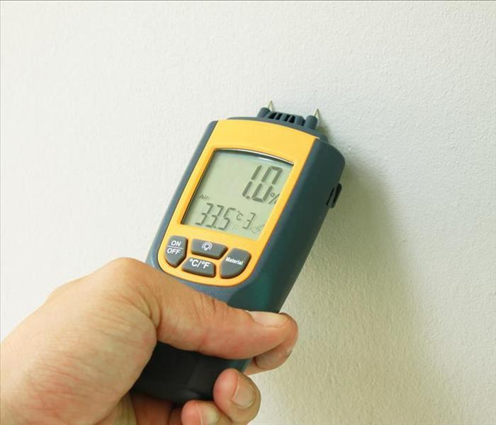 Yellow Moisture Meter pushed against a wall taking a digital reading