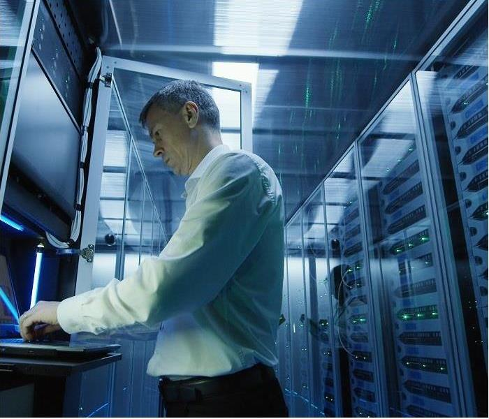 man standing while working on laptop in data storage room